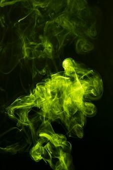 Fumo verde abstrato espalhado no fundo preto