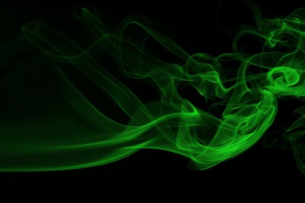 Fumo verde no conceito preto do fundo e da escuridão