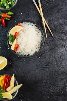 Funchosa de macarrão de arroz com legumes em uma tigela preta com pauzinhos em um fundo escuro, vista superior, flatlay.