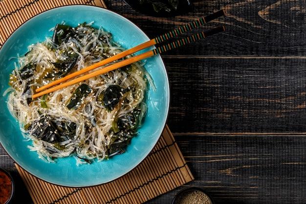 Funchoza salada com wakame em fundo escuro.