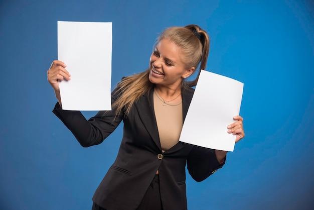 Funcionária controlando documentos e sorrindo.