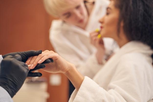 Funcionária de beleza habilidosa empurrando cuidadosamente as cutículas da cliente para trás usando um palito de laranja