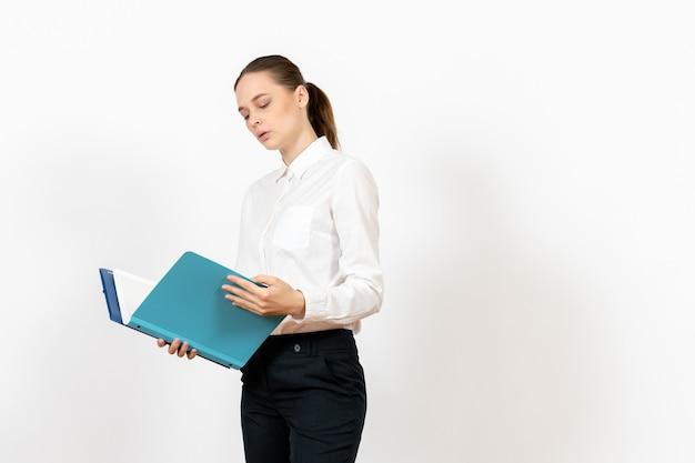 Funcionária de escritório com blusa branca segurando documentos no chão branco.