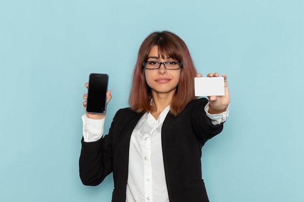 Funcionária de escritório feminina de terno estrito segurando o telefone e um cartão branco na superfície azul.