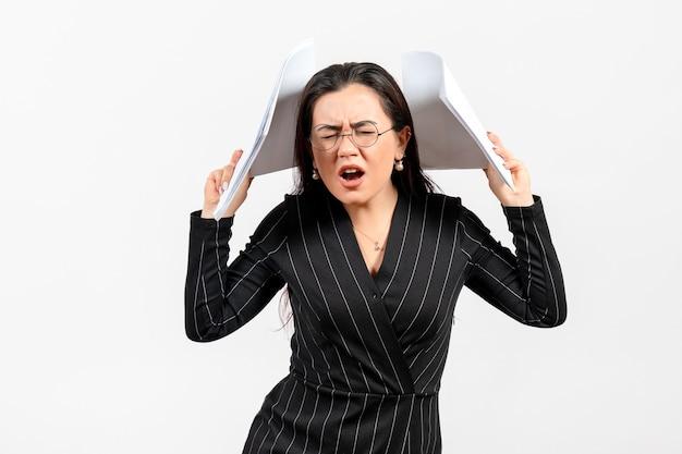 Funcionária de escritório vestida de terno preto com documentos em branco