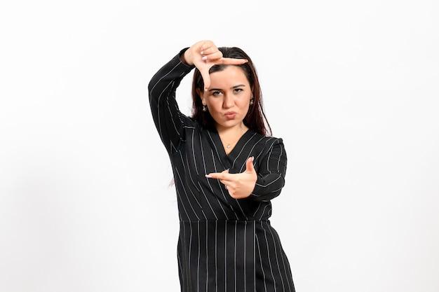 Funcionária de escritório vestida de terno preto, posando em branco.