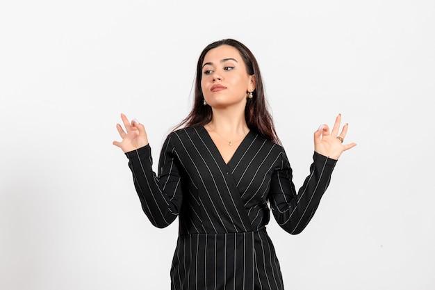 Funcionária de escritório vestida de terno preto, posando em branco