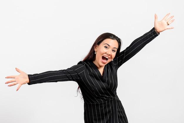 Funcionária de escritório vestida de terno preto, posando emocionalmente em branco