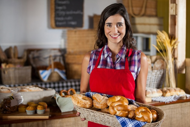 Funcionária feminina sorridente segurando uma cesta de vime com vários pães no balcão
