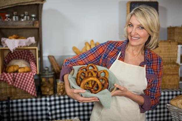 Funcionária feminina sorridente segurando uma cesta de vime de pão pretzel no balcão