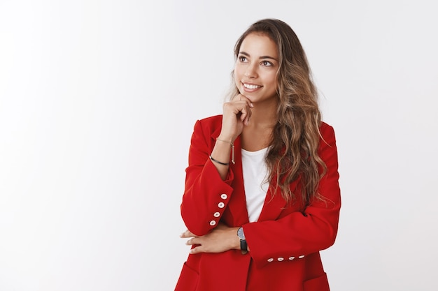 Funcionária habilidosa e criativa pensando em idéias, trabalhando em projetos importantes, olhando para cima, pensativa, satisfeita, sorrindo, tocando o queixo, pensando, tendo um plano, em pé, sonhadora, vestindo uma jaqueta formal vermelha
