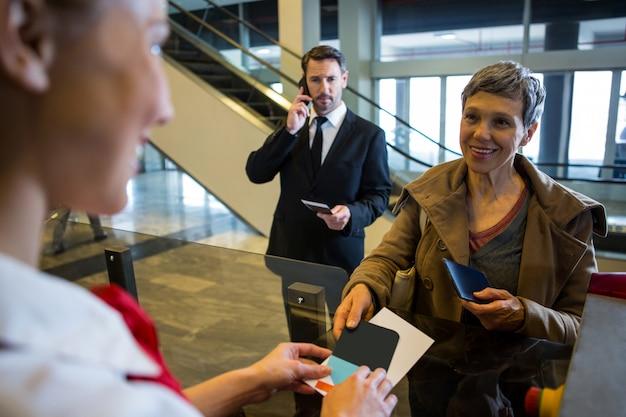 Funcionárias dando cartão de embarque ao passageiro