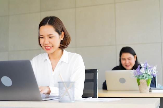 Funcionárias digitando no laptop para trabalhar com contabilidade ou fazer relatório no escritório para o conceito de estilo de vida e trabalho em equipe