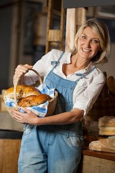 Funcionárias segurando uma cesta de alimentos doces na seção de padaria