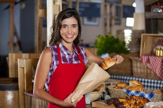 Funcionárias sorrindo embalando comida doce em um saco de papel no balcão de uma padaria