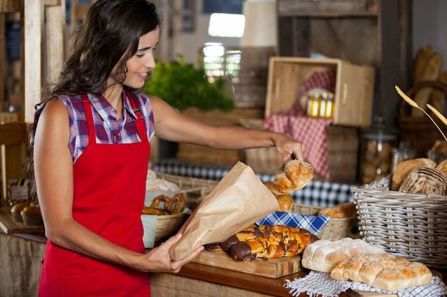 Funcionárias sorrindo embalando comida doce em um saco de papel no balcão