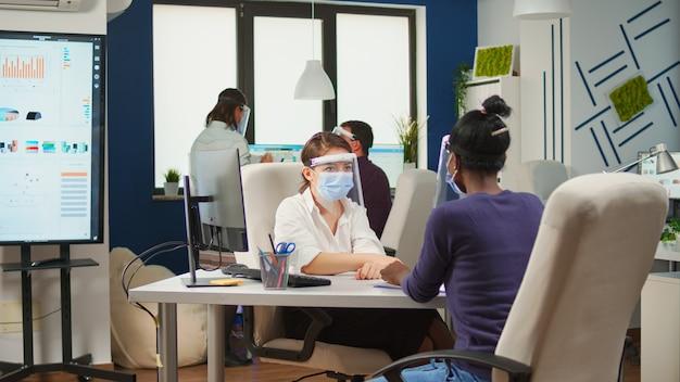 Funcionário africano e colega de trabalho com máscaras, planejando projeto financeiro, digitando no computador e discutindo sentado no escritório com o novo normal. equipe multiétnica respeitando a distância social