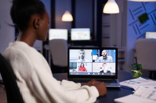 Funcionário africano trabalhando horas extras no escritório comercial tarde da noite, discutindo com parceiros on-line usando a webcam