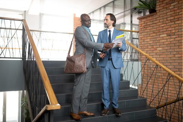 Funcionário apresentando relatório. funcionário de pele escura mostrando relatório ao chefe enquanto está na escada