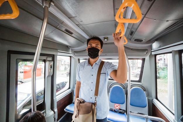 Funcionário asiático usando máscara para proteção em transporte público de passageiros em bonde