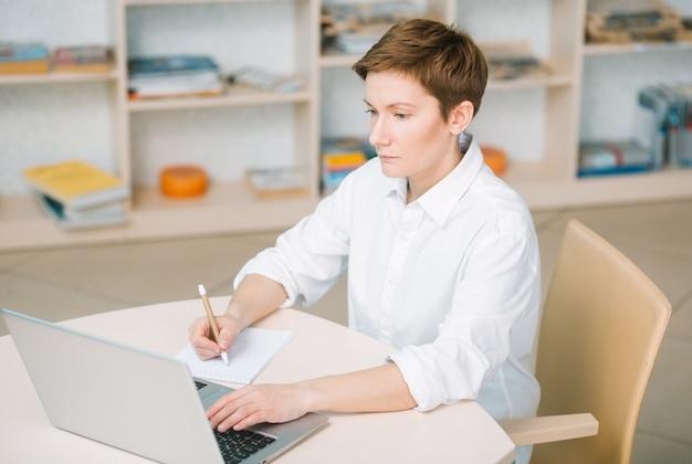 Funcionário bem sucedido em um escritório brilhante é concentrado e escreve informações
