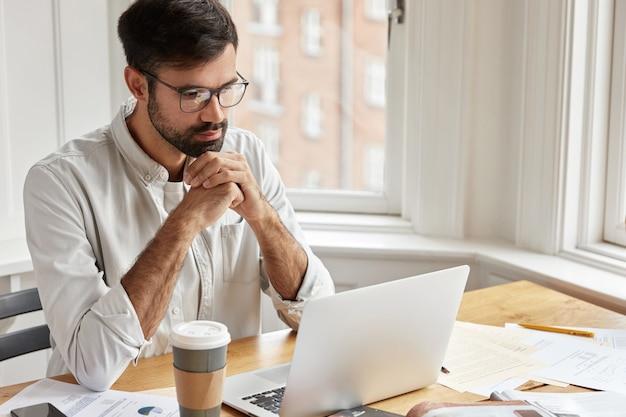 Funcionário bonito tem um olhar sério e concentrado no laptop, usa óculos transparentes e camisa branca, trabalha com um laptop,