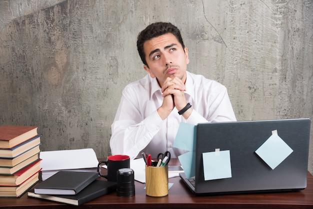 Funcionário cansado, olhando de cabeça para baixo na mesa do escritório.