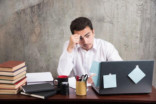 Funcionário cansado, olhando para o laptop na mesa do escritório.