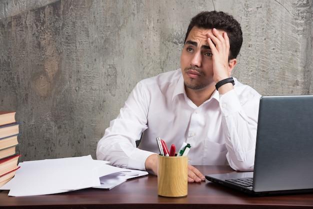 Funcionário cansado, sentado à mesa com folhas de papéis. foto de alta qualidade