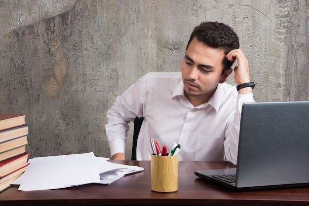 Funcionário cansado, sentado à mesa e olhando folhas de papel. foto de alta qualidade
