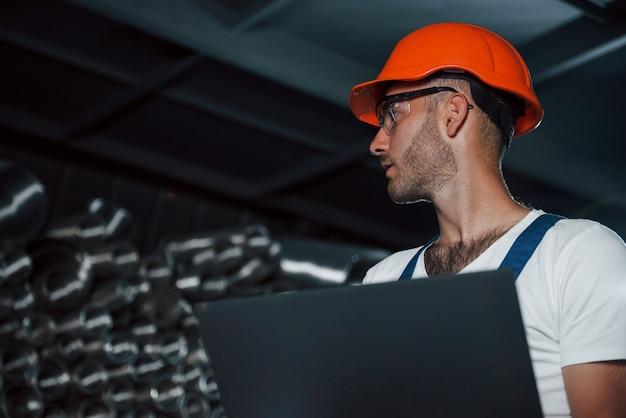 Funcionário com barba por fazer e óculos de proteção. homem de uniforme trabalha na produção. tecnologia industrial moderna.