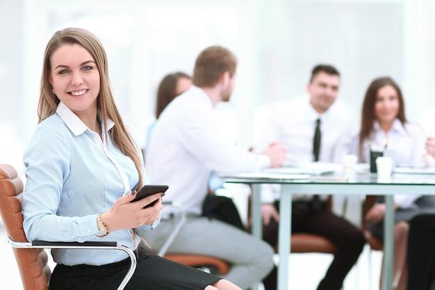 Funcionário com um smartphone no fundo da equipe de negócios