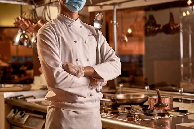 Funcionário da cozinha cruzando as mãos abaixo do peito enquanto fica ao lado de um fogão com panela e frigideira