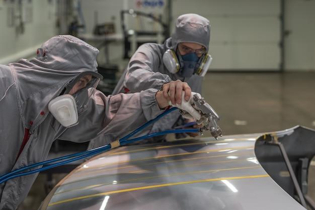 Funcionário da oficina de pintura da fábrica de automóveis realiza treinamento em pintura de partes corporais