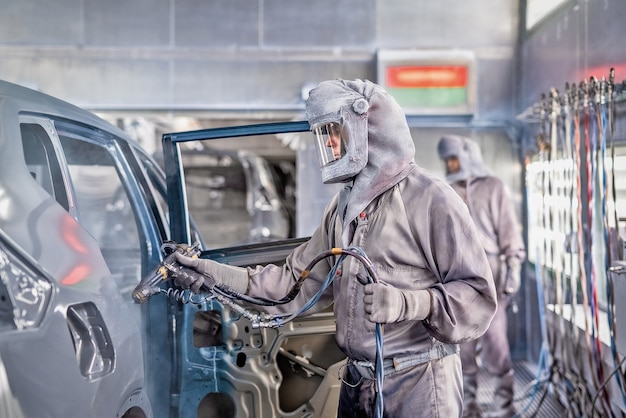 Funcionário da oficina de pintura de carroceria executa pintura.