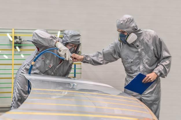 Funcionário da oficina de pintura de fábrica de automóveis realiza treinamento sobre pintura de partes corporais