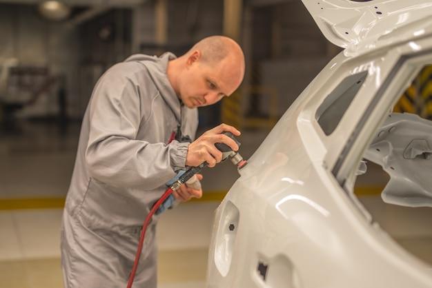Funcionário da oficina de pintura de uma fábrica de automóveis lixar a parte pintada com ferramenta pneumática