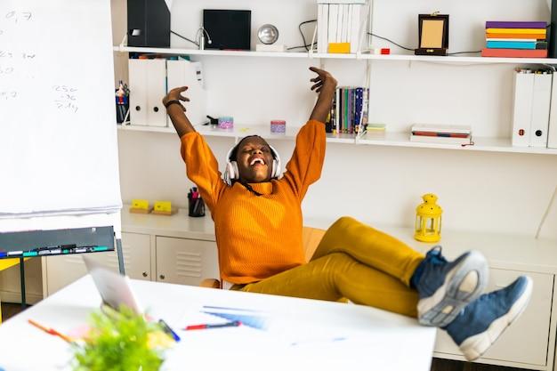 Funcionário de empresa de negócios descansando no escritório com fones de ouvido