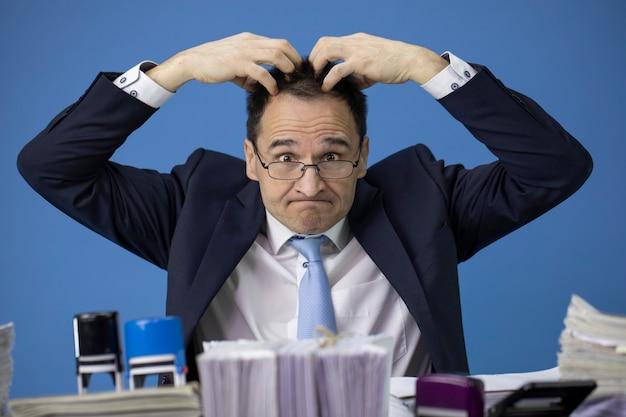 Funcionário de escritório cansado coçando a cabeça