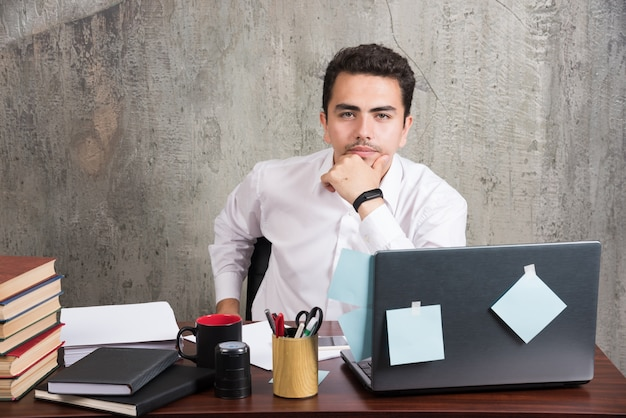 Funcionário de escritório pensando em trabalhar na mesa do escritório. Foto gratuita