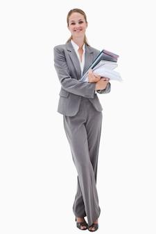 Funcionário de escritório sorridente com pilha de papelada