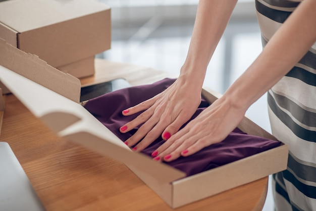 Funcionário de loja na internet preparando roupas para envio
