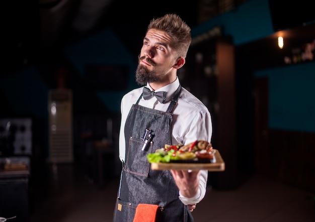 Funcionário de restaurante carismático serve pratos de forma prestativa