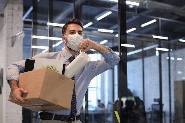 Funcionário demitido em um coronavírus epidêmico. trabalhador demitido saindo do escritório com seu material de escritório.