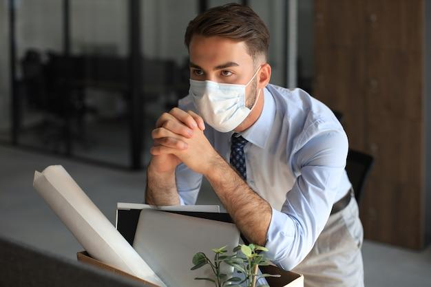 Funcionário demitido em um coronavírus epidêmico. trabalhador despedido triste está levando seu material de escritório com ele do escritório.