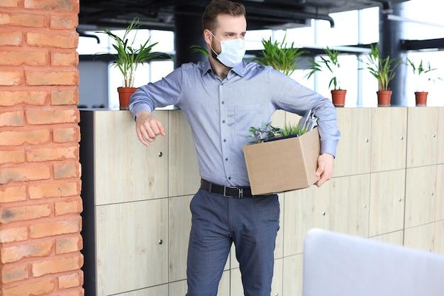 Funcionário demitido em uma epidemia de coronavírus covid-19. trabalhador demitido saindo do escritório com seu material de escritório
