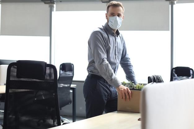 Funcionário demitido em uma epidemia de coronavírus covid-19. trabalhador despedido triste está levando seu material de escritório com ele do escritório