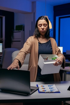 Funcionário deprimido após ser despedido com uma caixa de papelão nas mãos. mulher triste segurando seus pertences tarde da noite no escritório depois de ser demitida do trabalho. empresária despedida, crise econômica