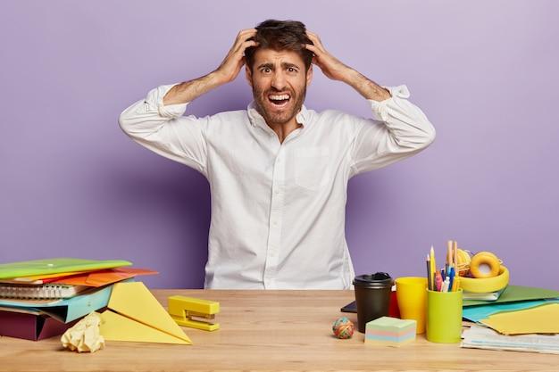 Funcionário deprimido sentado na mesa do escritório