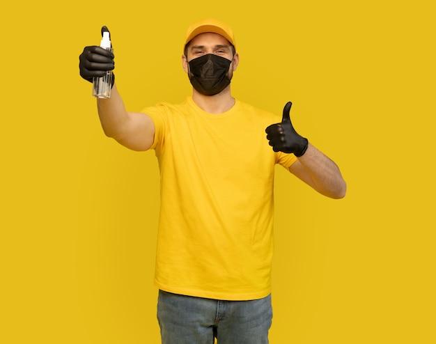 Funcionário do entregador em uniforme de camiseta amarela, máscara facial estéril, garrafa com luva e sabão desinfetante isolado